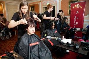 Парикмахе ухаживает за волосами клиентки